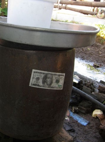 Hell money glued onto the water urn, in case the gods of prosperity and commerce are feeling a bit thirsty.
